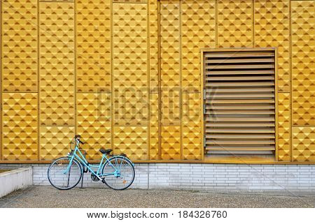 Berlin, Germany - April 12, 2017: Blue parked bicycle on the background of the yellow wall of the Berlin Philharmonic.