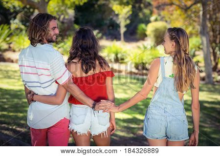 Rear view of man cheating on her woman in park while walking