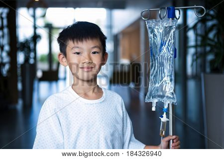 Smiling boy patient holding intravenous iv drip stand in corridor at hospital