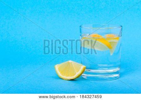 Glass of water with lemon in the morning on a blue background. Empty space for text