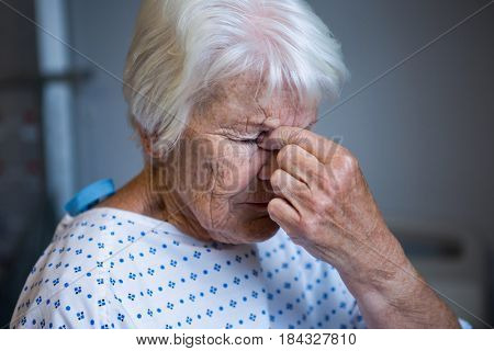Close-up of tensed senior patient standing at hospital