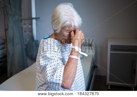 Tensed senior patient standing at hospital