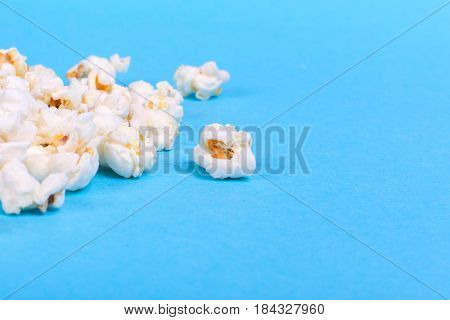 lot of popcorn scattered on a blue background. Empty space for text