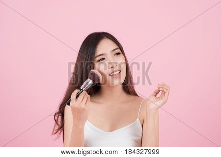 Beauty Asian Girl tan skin with Makeup Brushes. She smiling and looking to powder brush Natural makeup with beautiful v-shape face and long hair style.