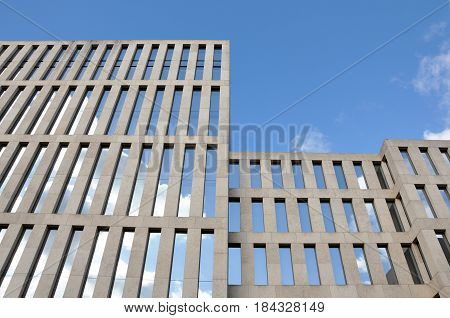 Berlin, Germany - April 13, 2017: Modern building of Jacob and Wilhelm Grimm Center with rows of vertical windows reflecting the blue sky. Look up.