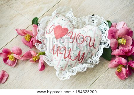 Textile handmade heart with the inscription I love mum and red roses petals on a wooden background. A Happy Mother's Day theme.