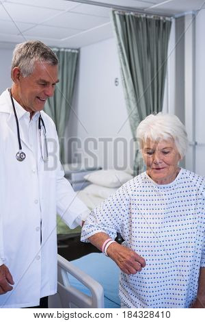 Doctor assisting senior patient in ward at hospital