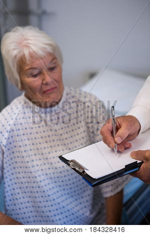 Doctor writing medical details of a senior patient in hospital