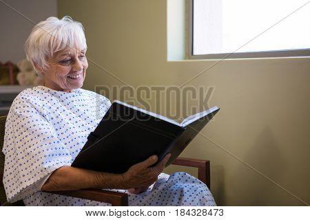 Happy senior patient reading book