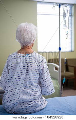 Rear-view of thoughtful senior patient sitting at hospital