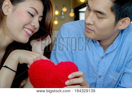 Lovers are showing affection for each other in a coffee shop.