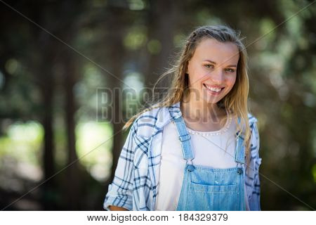 Portrait of smiling woman standing in park on a sunny day