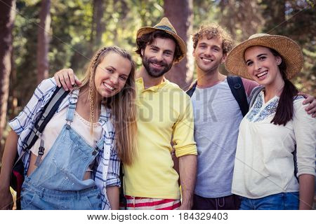 Portrait of smiling friends standing together with arm around in forest on a sunny day
