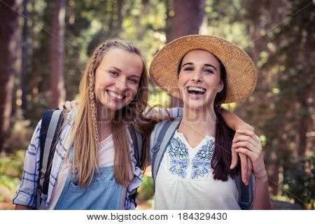 Portrait of smiling friends standing together with arm around in forest