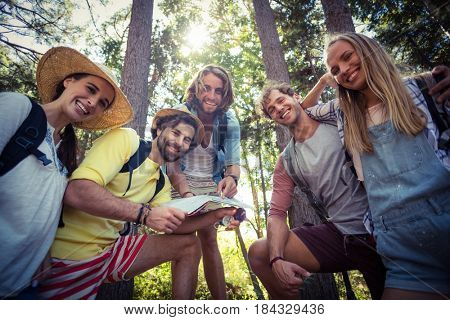 Portrait of smiling friends standing together in forest on a sunny day