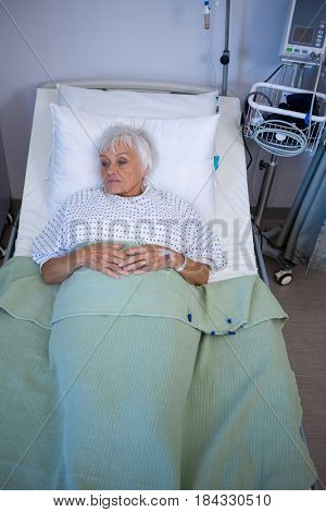 Thoughtful senior patient lying on bed in hospital