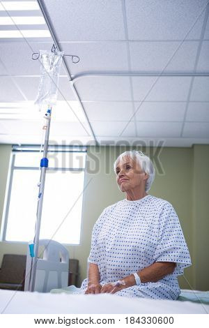 Worried senior patient sitting on bed in hospital