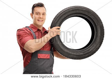 Young mechanic with a tire looking at the camera and smiling isolated on white background