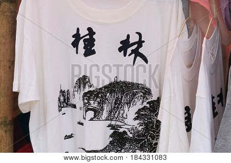 YANGSHOU CHINA - NOVEMBER 19, 2016: Xingping street market souvenir shop sells Guilin t-shirt.