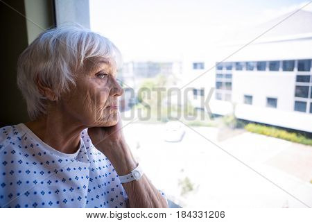 Thoughtful senior patient looking through window in hospital