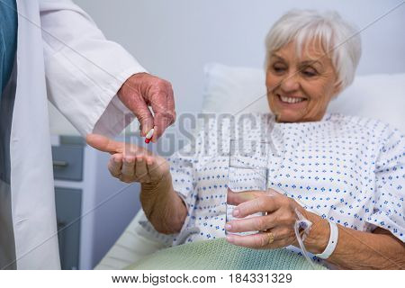 Doctor giving medicine pill to senior patient in hospital