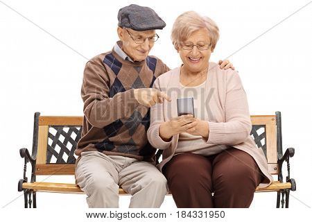 Happy senior couple sitting on a bench and looking at a phone isolated on white background