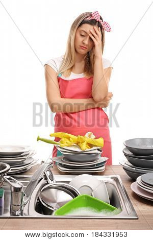 Young woman behind a sink filled with dirty plates holding her head in disbelief isolated on white background