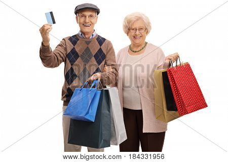 Cheerful seniors with a credit card and shopping bags isolated on white background