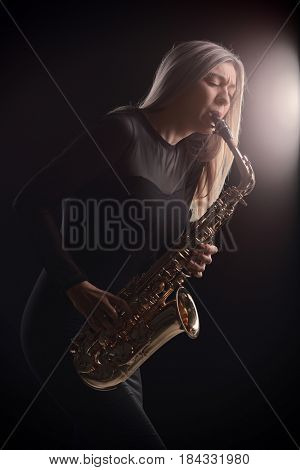 Female jazz musician playing a saxophone during a concert