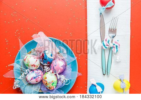 Decorated eggs on plate at red table with fork and knife