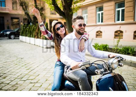 Beautiful Young Couple Riding Scooter Along A Street And Smiling