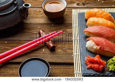 Photography of sushi, red sticks, soy sauce on wooden table
