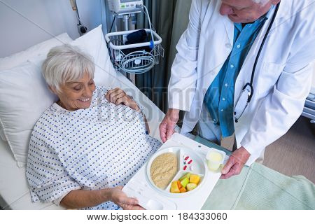 Doctor serving breakfast and medicine to senior patient in hospital