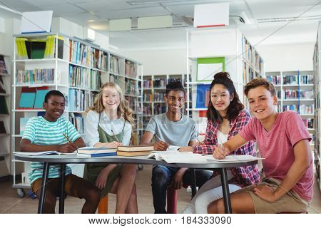 Portrait of happy classmates studying in library at school