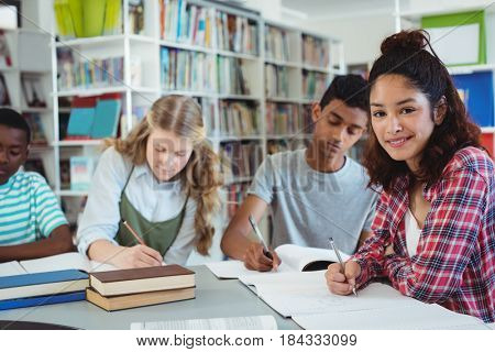 Portrait of happy schoolgirl studying with her classmates in library at school