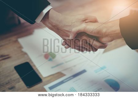 two business man partner shaking hand on working table with vintage filter