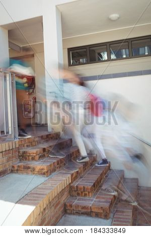 Blur view of students moving up staircase at school