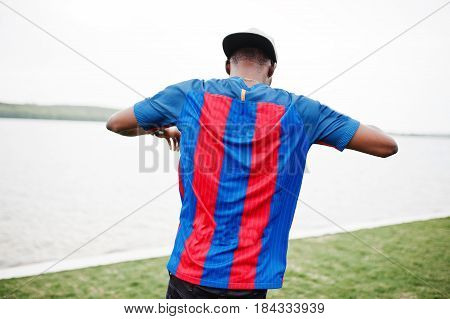 Stylish African American Boy Wear At Cap, Football T-shirt Showing His Back Against Lake. Black Spor