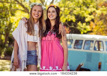 Two smiling friends standing together in park