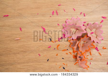 Close-up of colored pencils shavings on a wooden background