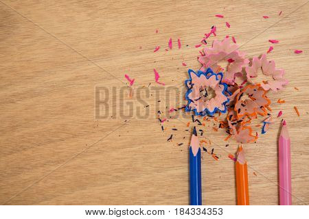 Close-up of colored shavings with colored pencils on wooden background