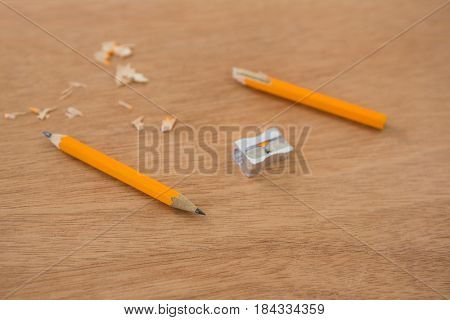 Broken yellow pencil with sharpener on wooden background