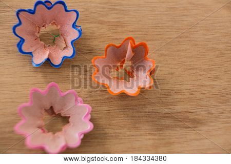 Close-up of colored pencil shavings in a flower shape on wooden background