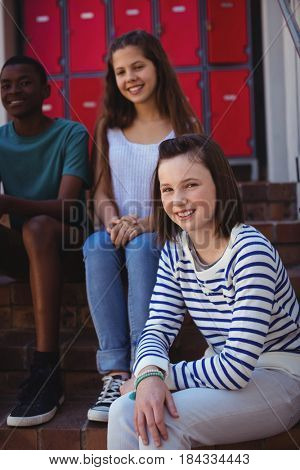 Portrait of students sitting on staircase at school