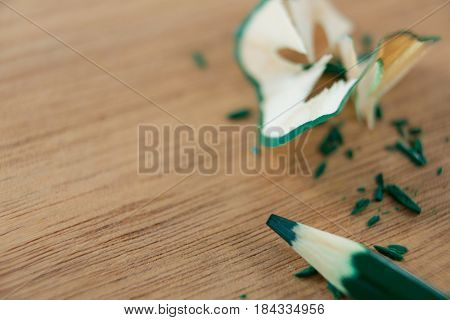 Close-up of green color pencil with pencil shaving on wooden background
