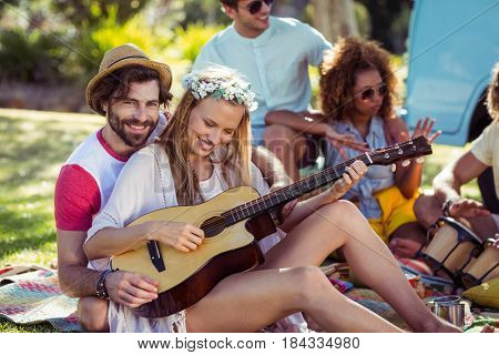 Group of friends having fun and playing music in park