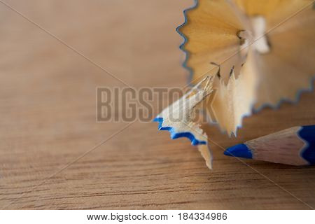 Close-up of blue color pencil with pencil shaving on wooden background