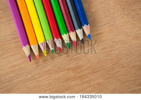 Colored pencils arranged in a row on wooden background