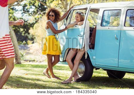 Friends having fun near campervan in park