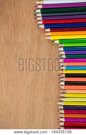 Colored pencils arranged in diagonal line on wooden background